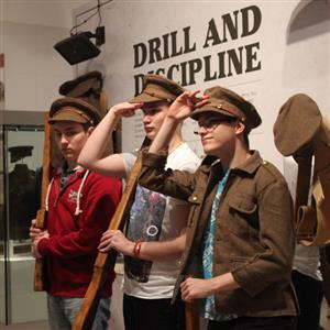 Three young men try on old army uniforms in a museum