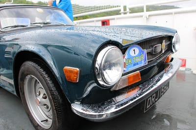 a classic car's headlamp and bonnet